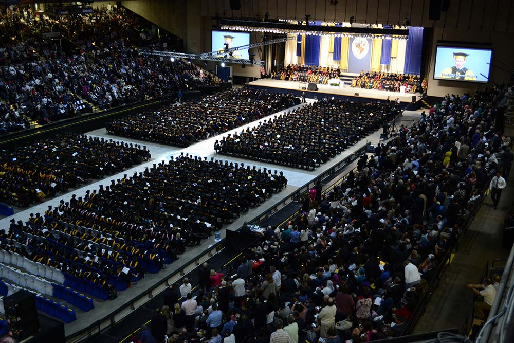 Ariel perspective photo of Commencement ceremony. Graduates sitting in chairs on floor of Arena and spectators looking on.