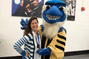 Volunteer escorting Jay, the mascot