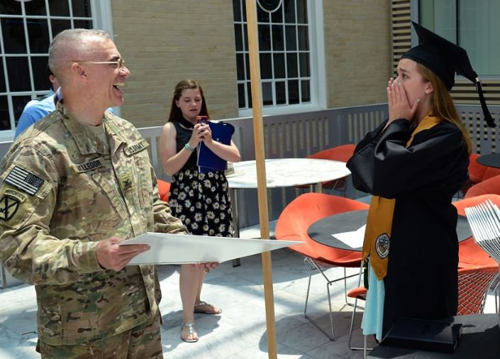 Photo of graduate being surprised by her father who has been serving in Afghanistan as he presents her with her diploma.