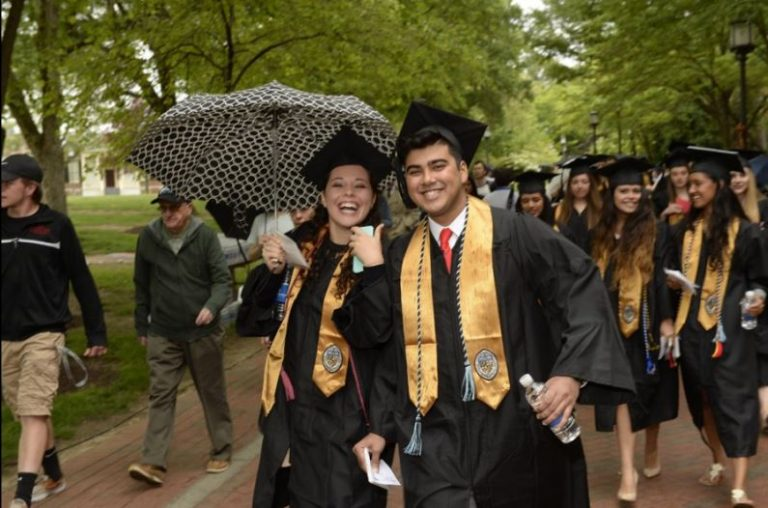 Photo of smiling graduates walking toward ceremony, one holding an umbrella.
