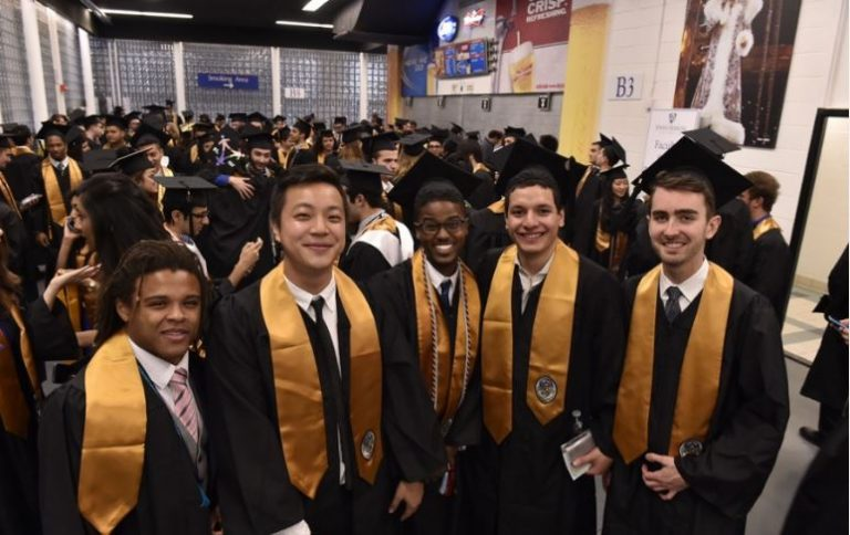 Photo of five smiling graduates with a sea of graduats congregating behind them.