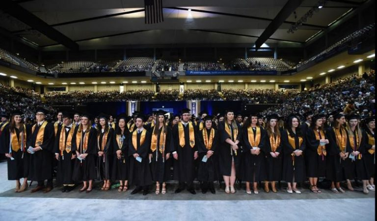 Photo of graduates standing in front of seats with full stands in the background.