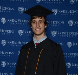 Graduate in front of a Johns Hopkins branded backdrop