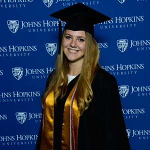 Photo of a graudate in fron of a Johns Hopkins University branded backdrop.