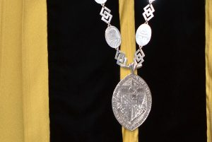Up-close photo of the Chain, against black and gold doctoral robe.