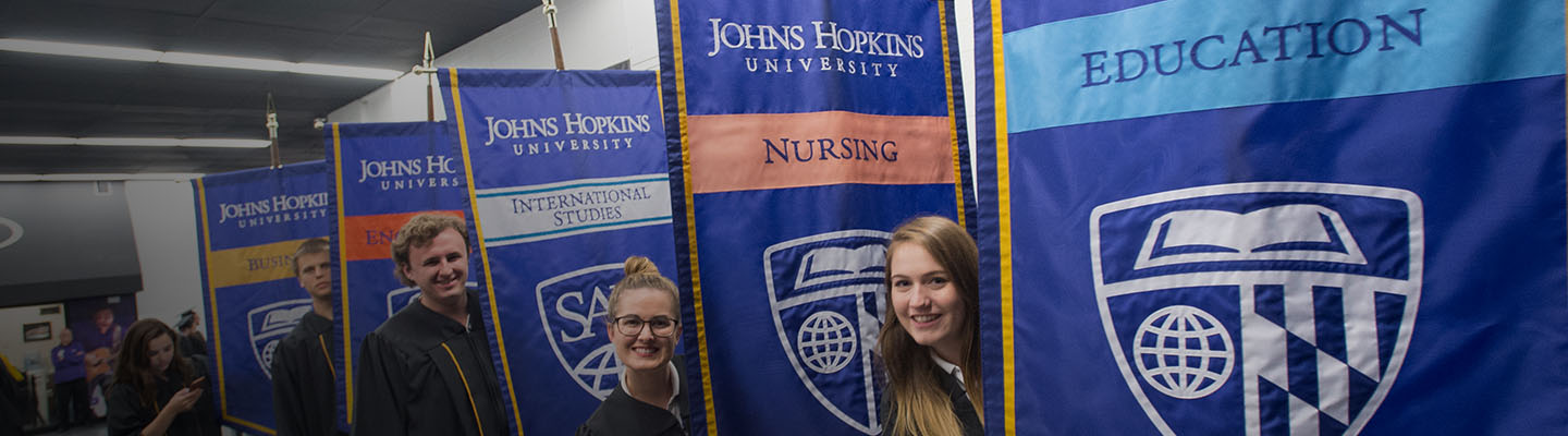Banner carriers posing with gonfalons that display five schools within the niversity- Business, Engineering, International Studies, Nursing, and Education.
