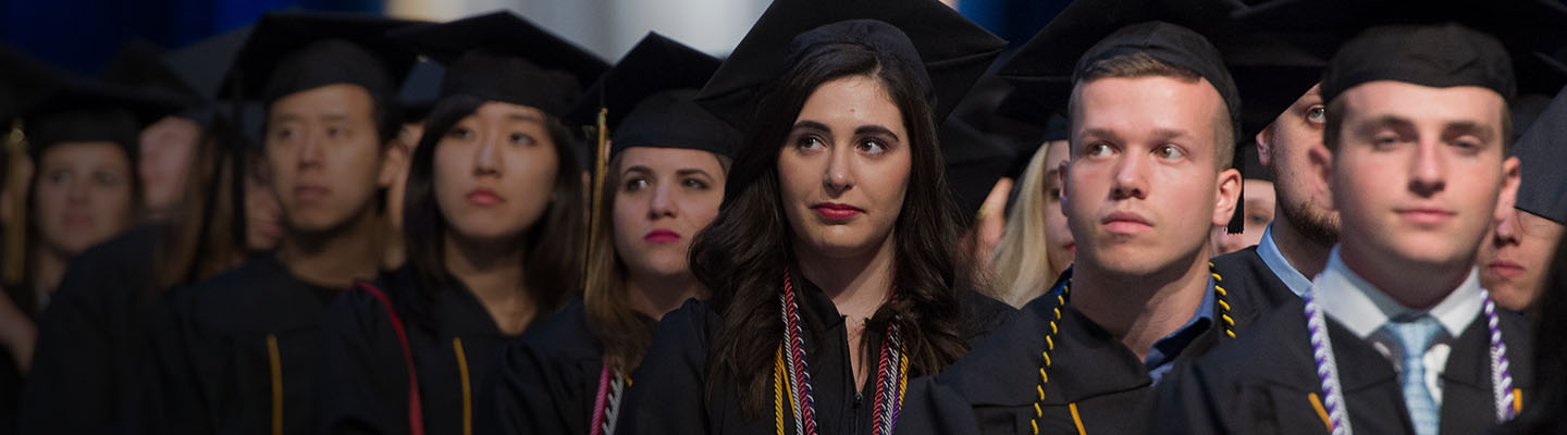 Rows of students intently look up toward the stage during the ceremony.