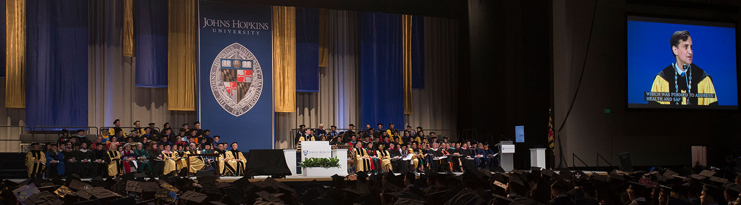 Photo of the stage from the student's perspective on the lower level of the arena. President Daniels is speaking at the podium.