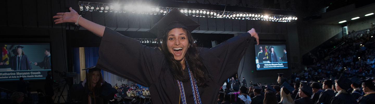 Female student smiles big for the camera, with arms stretched out in excitement of her accomplishment. Stage is in the background.