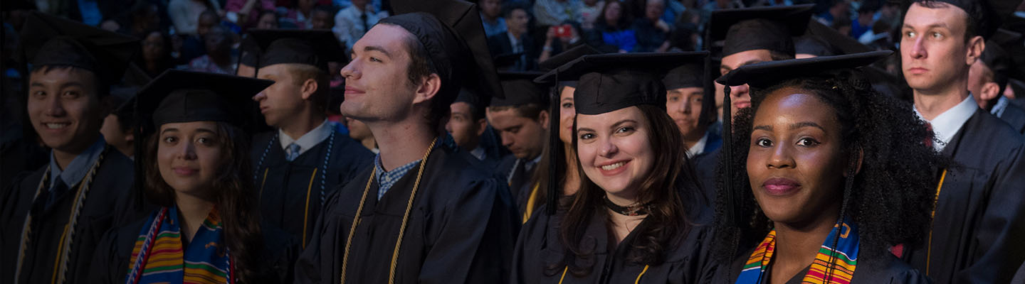 Students stand at their seats, looking toward the stage, during the ceremony, with full stands in the background.