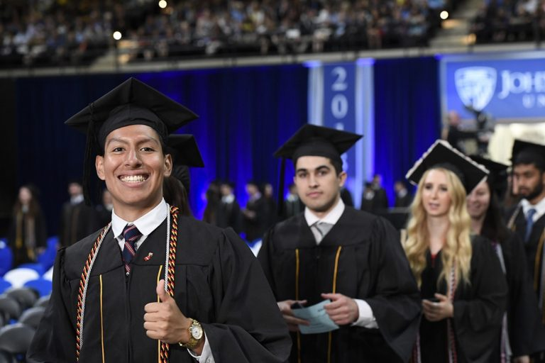 Picture of graduate walking into arena